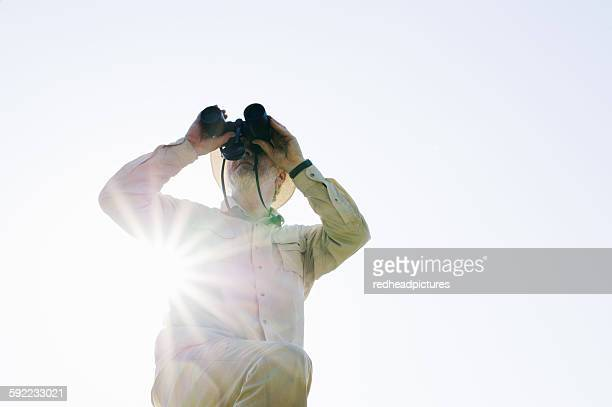 Low angle view of senior man in sunlight looking through binoculars