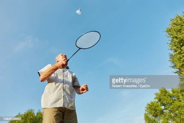 low angle view of senior man playing badminton against blue sky - badminton stock pictures, royalty-free photos & images