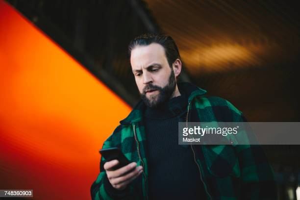Low angle view of serious man using mobile phone by orange billboard at railroad station