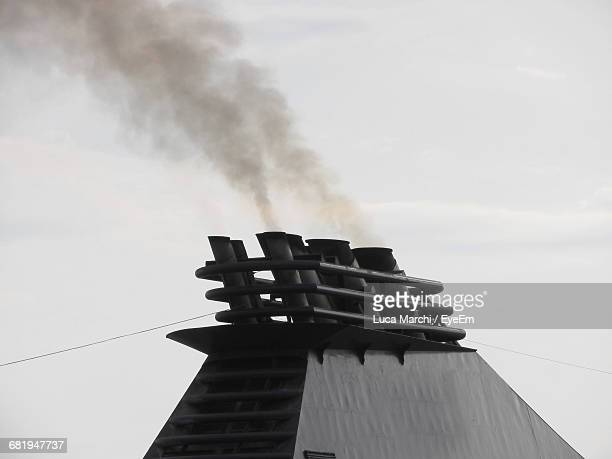 low angle view of ship funnel emitting smoke against sky - ship funnel stock photos and pictures