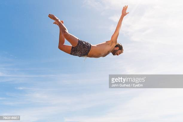 Low Angle View Of Shirtless Man Jumping In Mid-Air Against Sky