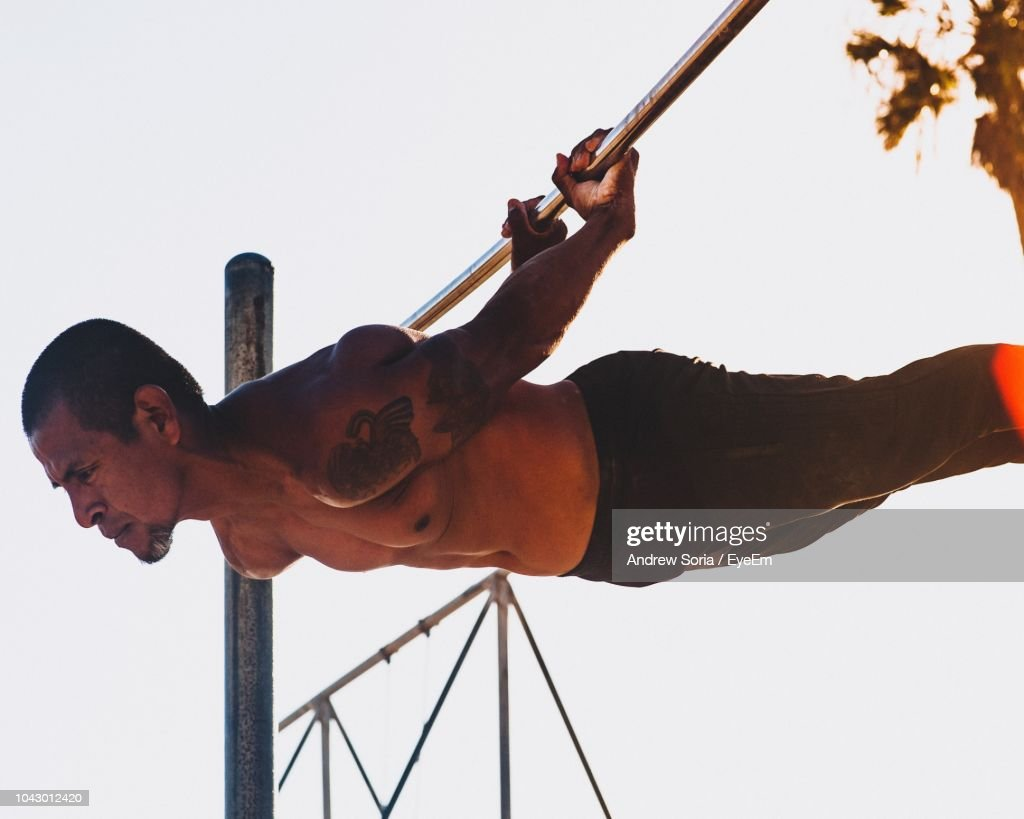 Low Angle View Of Shirtless Mature Man Exercising On Pole Against Clear Sky : Stock Photo