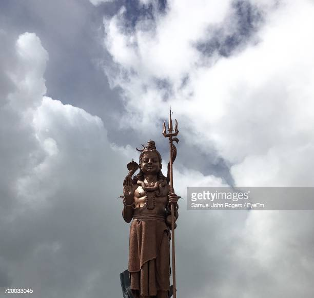 Low Angle View Of Shiva Statue Against Cloudy Sky