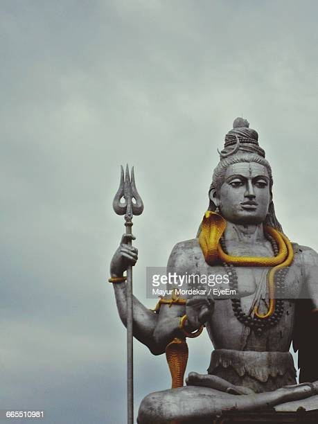 low angle view of shiva statue against sky at murudeshwara - shiva stock photos and pictures