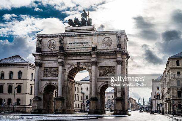 Low Angle View Of Siegestor With Buildings Against Cloudy Sky