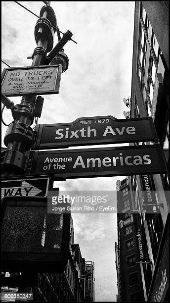 low angle view of sign board by buildings against cloudy sky - filho stockfoto's en -beelden