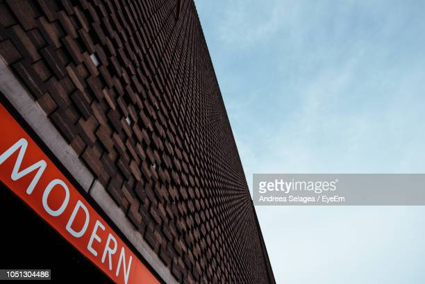 Low Angle View Of Sign On Building Against Sky