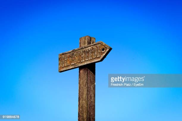 Low Angle View Of Sign On Pole Against Clear Blue Sky