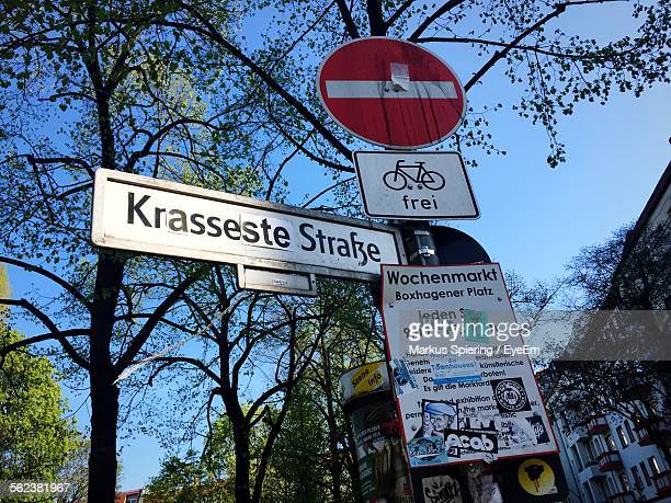 Low Angle View Of Signboards By Trees Sky