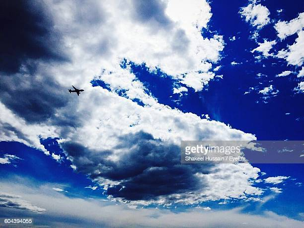 Low Angle View Of Silhouette Airplane Against Cloudy Blue Sky