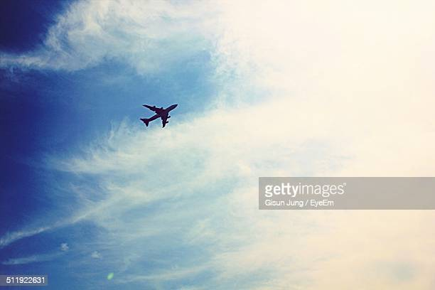 Low angle view of silhouette airplane against cloudy sky