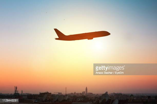 Low Angle View Of Silhouette Airplane Against Sky During Sunset