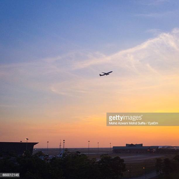 low angle view of silhouette airplane flying against sky during sunset at kuala lumpur international airport - kuala lumpur international airport stock photos and pictures