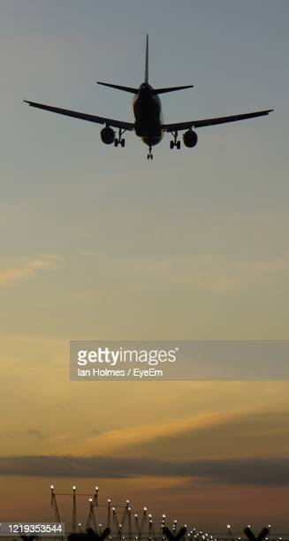 low angle view of silhouette airplane flying against sky during sunset - industry stock pictures, royalty-free photos & images
