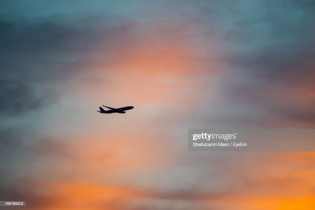 Low Angle View Of Silhouette Airplane Flying Against Sky During Sunset : Stock Photo