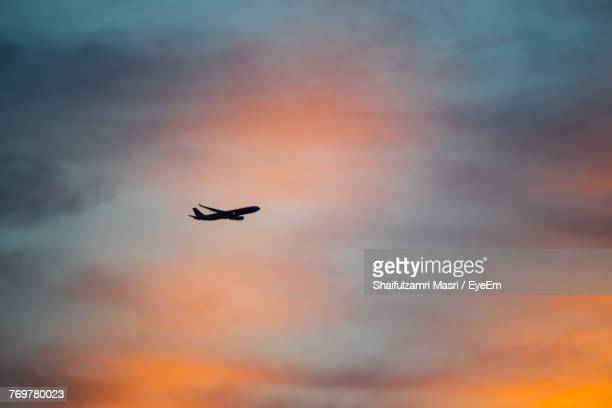 low angle view of silhouette airplane flying against sky during sunset - shaifulzamri stock-fotos und bilder