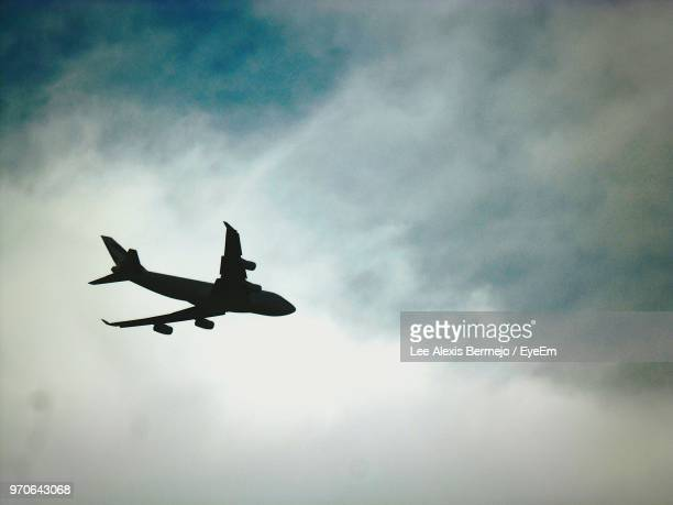 Low Angle View Of Silhouette Airplane Flying In Cloudy Sky