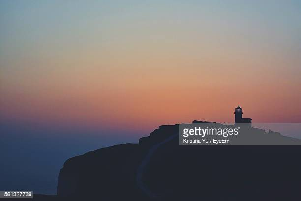low angle view of silhouette belle tout lighthouse on mountain against sky at sunset - belle tout lighthouse stock photos and pictures
