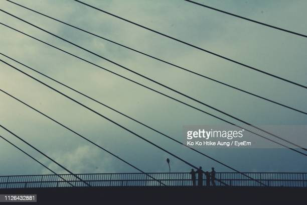 low angle view of silhouette bridge against cloudy sky during sunset - ko ko htike aung stock pictures, royalty-free photos & images