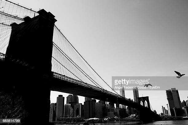 Low Angle View Of Silhouette Brooklyn Bridge Over East River In City