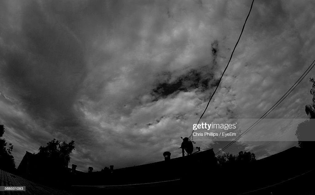 Low Angle View Of Silhouette Building Against Cloudy Sky : Stock Photo