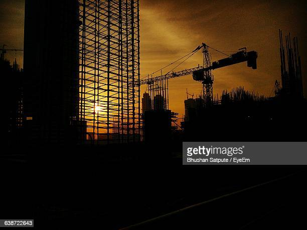 Low Angle View Of Silhouette Building And Crane Against Orange Sky