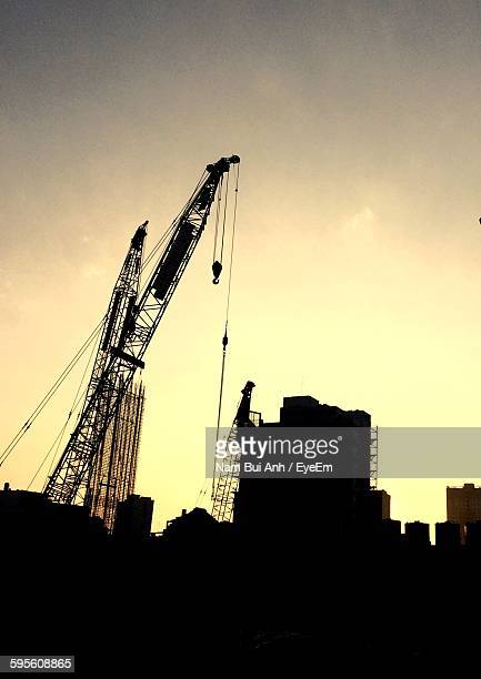 Low Angle View Of Silhouette Building And Crane Against Sky