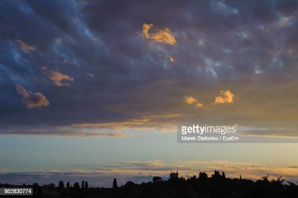 low angle view of silhouette buildings against dramatic sky - marek stefunko stockfoto's en -beelden
