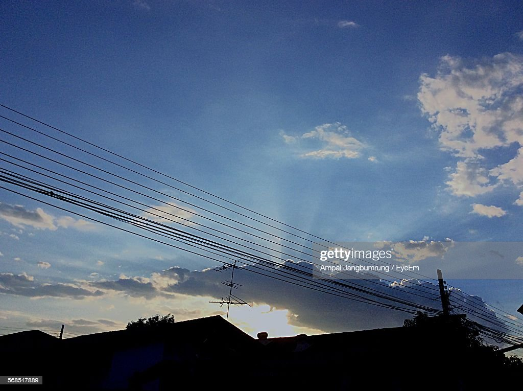 Low Angle View Of Silhouette Cables Over Residential Houses Against Sky : Stock Photo