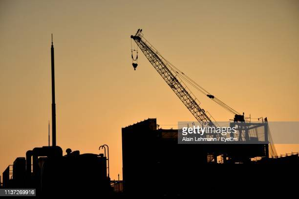low angle view of silhouette crane against sky during sunset - crane construction machinery stock pictures, royalty-free photos & images