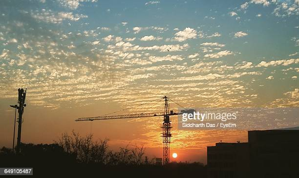 Low Angle View Of Silhouette Crane By Building At Sunset