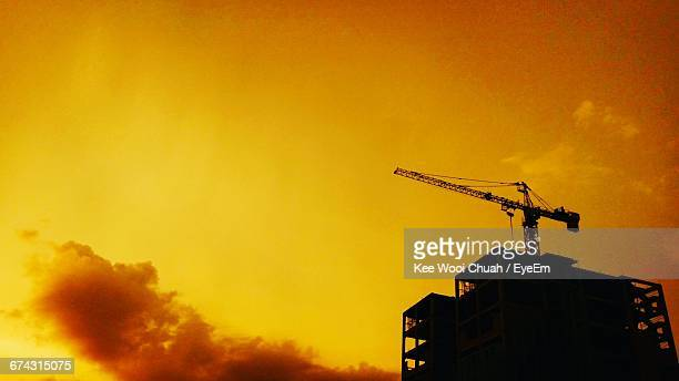 Low Angle View Of Silhouette Crane On Incomplete Building Against Orange Sky During Sunset