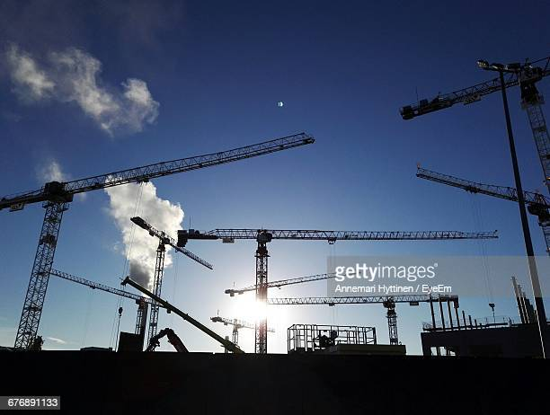 Low Angle View Of Silhouette Cranes At Construction Site Against Blue Sky During Sunny Day