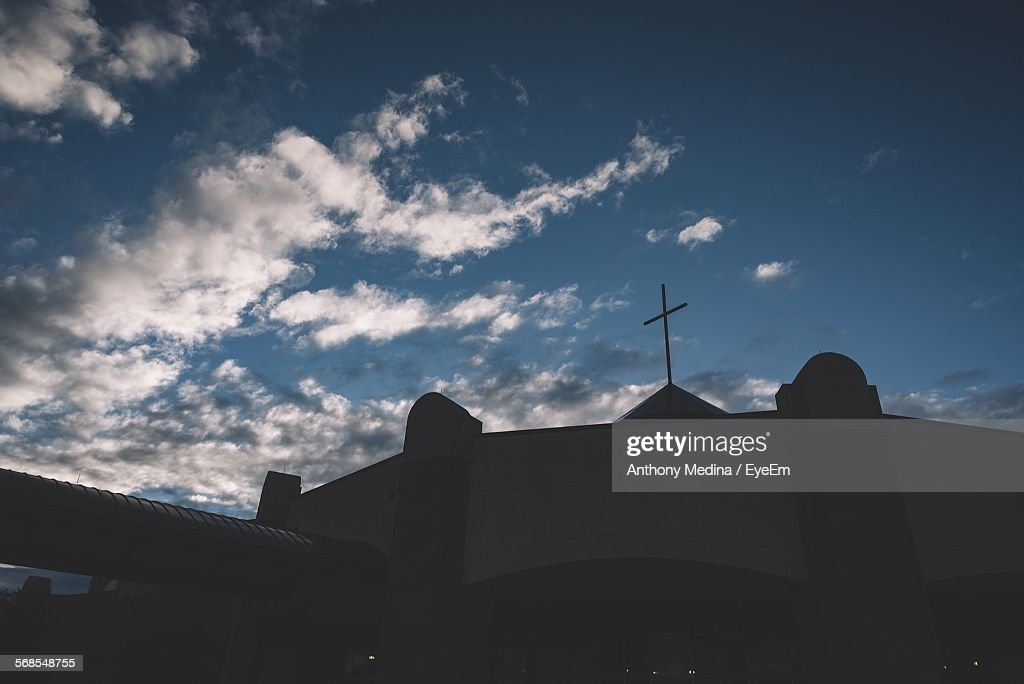 Low Angle View Of Silhouette Cross On Church Against Cloudy Sky At Dusk : Stock Photo