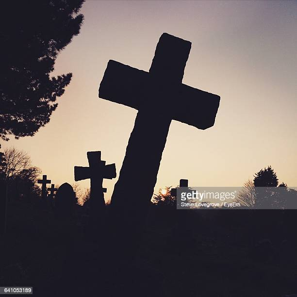 Low Angle View Of Silhouette Crosses At Cemetery During Sunset