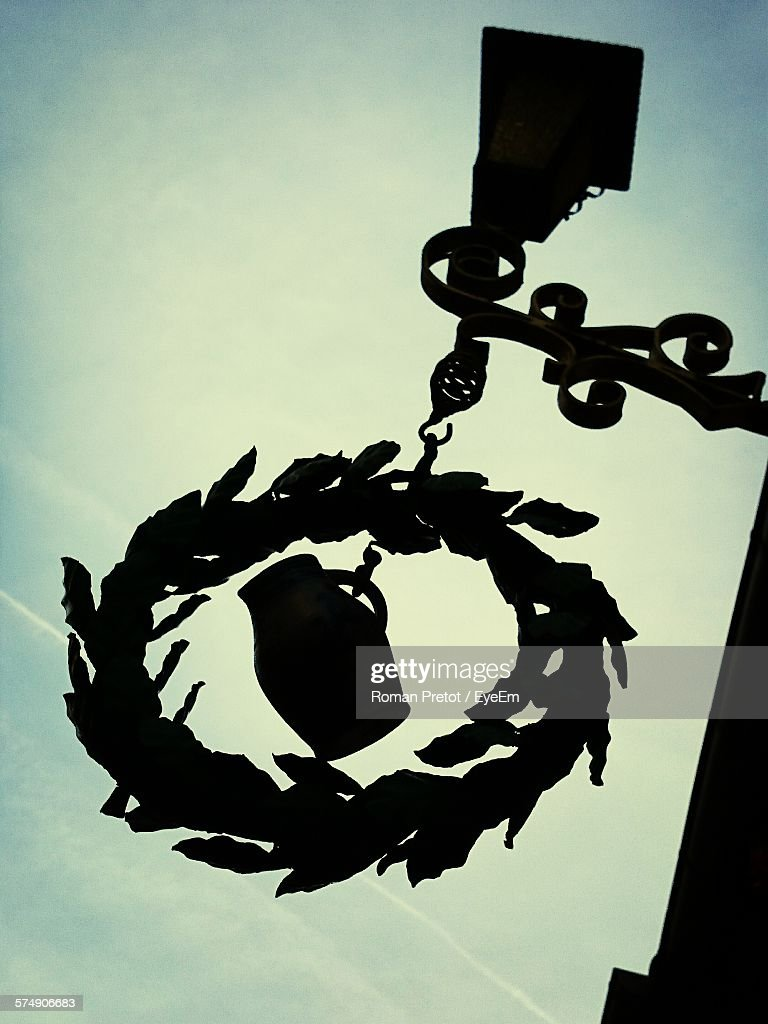 Low Angle View Of Silhouette Decoration Hanging From Lamp Against Sky : Stock-Foto