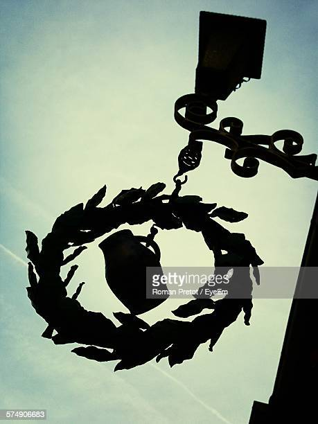 low angle view of silhouette decoration hanging from lamp against sky - roman pretot stock-fotos und bilder