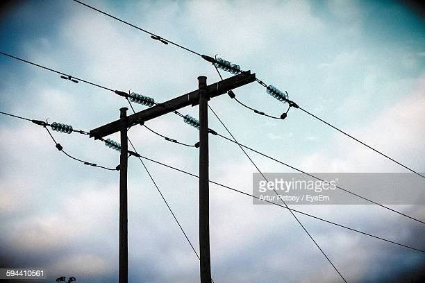 low angle view of silhouette electricity pylon against cloudy sky - artur petsey foto e immagini stock