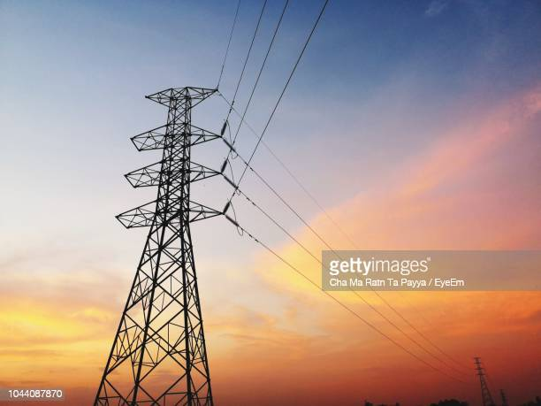 low angle view of silhouette electricity pylon against dramatic sky during sunset - elettricità foto e immagini stock