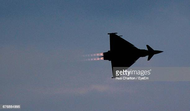 Low Angle View Of Silhouette Fighter Plane Flying In Sky