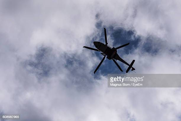 Low Angle View Of Silhouette Helicopter Against Cloudy Sky