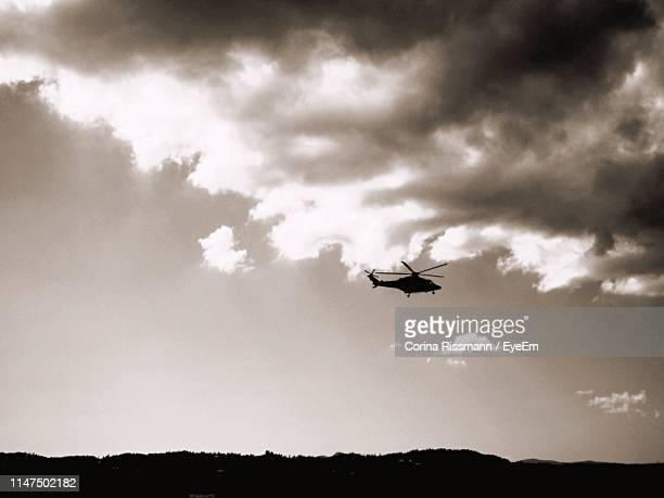 low angle view of silhouette helicopter flying against sky - corina rissmann stock-fotos und bilder