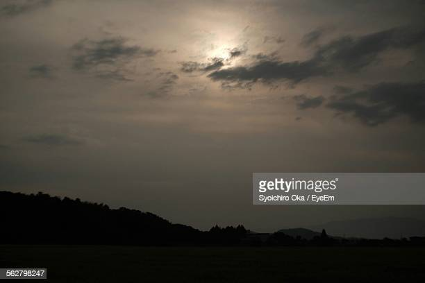 low angle view of silhouette hill against sky at sunset - syoichiro oka stock-fotos und bilder