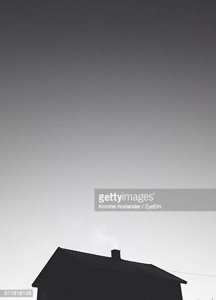 Low angle view of silhouette house against clear sky