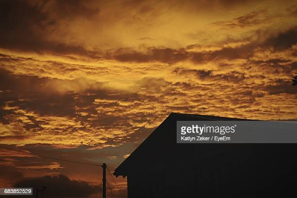 Low Angle View Of Silhouette House Against Cloudy Sky During Sunset
