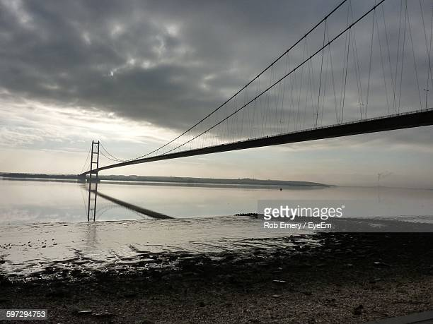 Low Angle View Of Silhouette Humber Bridge Over River At Sunset