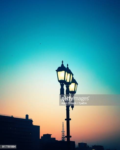Low Angle View Of Silhouette Illuminated Street Light Against Clear Sky At Dusk