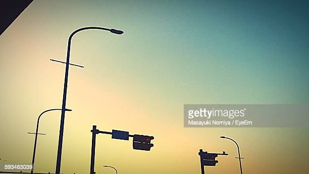 Low Angle View Of Silhouette Lighting Equipment Against Sky During Sunset