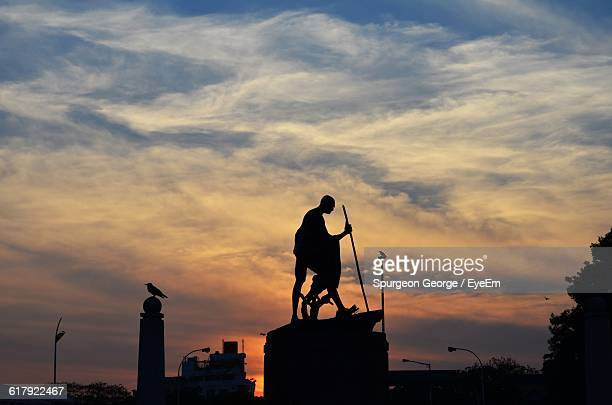 Low Angle View Of Silhouette Mahatma Gandhi Statue Against Cloudy Sky