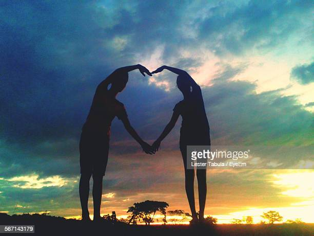 Low Angle View Of Silhouette Man And Woman Making Heart Shape From Hands During Sunset
